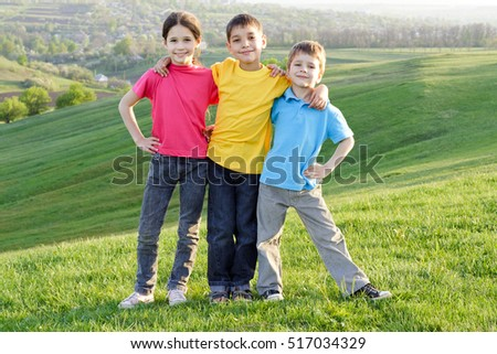 Group of happy kids standing on the green grass on the hillside.