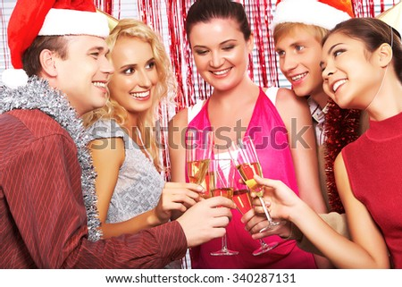Group of happy men and women in Santa caps toasting for Christmas
