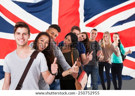 Group Of Happy Multi Ethnic Students Standing In Front Of Uk Flag Showing Thumb Up - stock photo