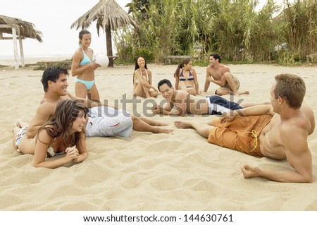 Group of happy multiethnic young friends relaxing on the beach - stock photo
