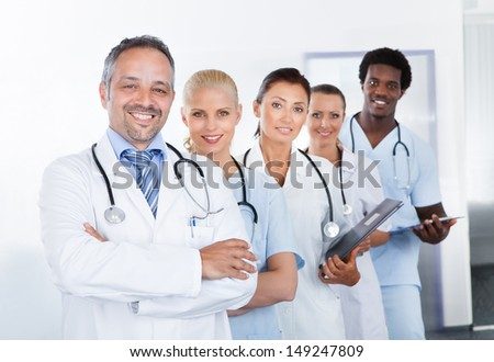 Group Of Happy Multiracial Doctors Standing In A Row - stock photo