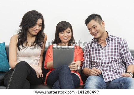 Group of Happy Pan-Asian friends hanging out together at home using Digital Tablet - stock photo