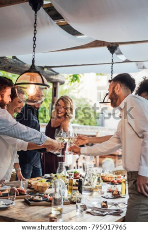 Group of happy people cheering with wine and rising glasses on celebration at restaurant.