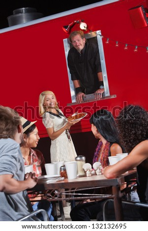 Group of happy people eating near a canteen