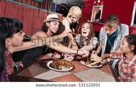 Group of happy people eating out at mobile restaurant - stock photo
