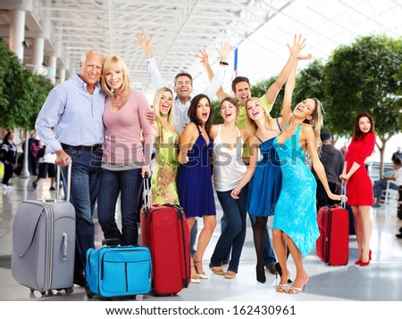 Group of happy people in airport. Holiday travel background. - stock photo