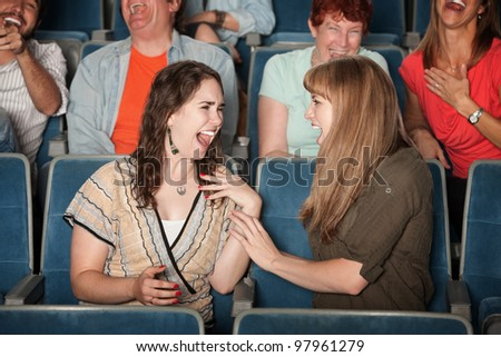Group of happy people laughing in a theater - stock photo
