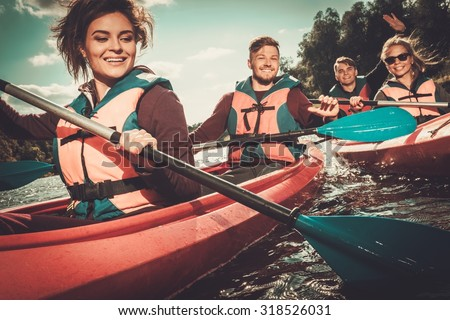 Group of happy people on a kayaks - stock photo