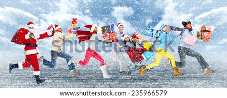 Group of Happy people running with Xmas gifts. Christmas. - stock photo