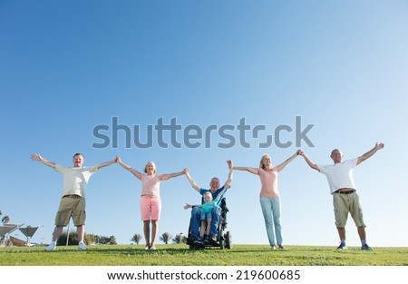 Group of Happy People smiling and show unity with disabled man. - stock photo