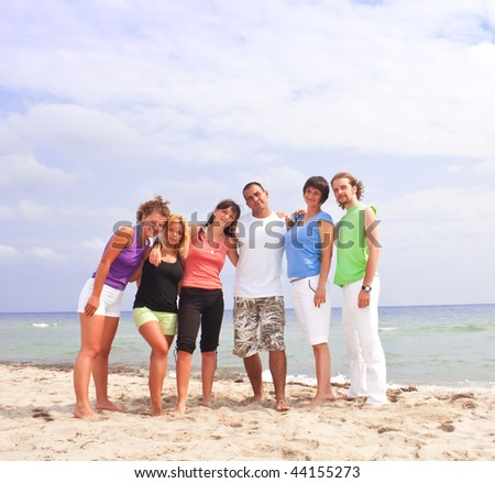 group of happy people standing on the beach