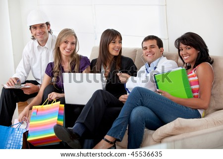 Group of happy people with different professions sitting on a sofa