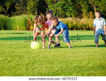 Group of happy preschool kids catching the ball - stock photo