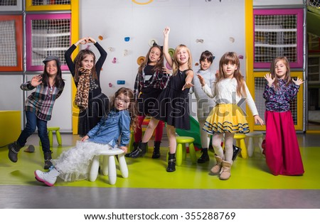 Group of  happy preschoolers dancing in playroom - stock photo
