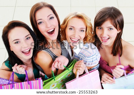 Group of happy pretty laughing girls with shopping bags, high ange view. - stock photo