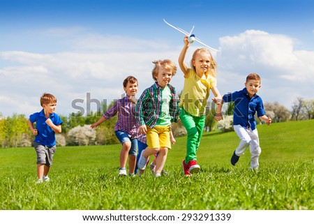 Group of happy running kids with white airplane - stock photo