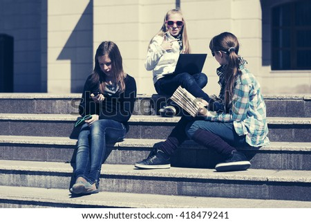 Group of happy school girls sitting on steps in campus - stock photo