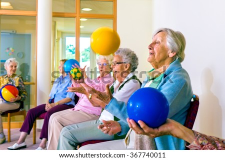 Group of happy senior ladies doing coordination exercises in a seniors gym sitting in chairs throwing and catching brightly colored balls - stock photo