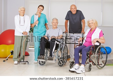 Group of happy senior people at physiotherapy in a nursing home with geriatric nurse - stock photo