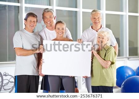 Group of happy senior people holding empty white advertising sign - stock photo