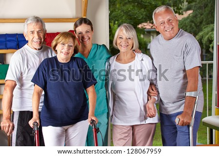 Group of happy senior people in gym with physiotherapist - stock photo