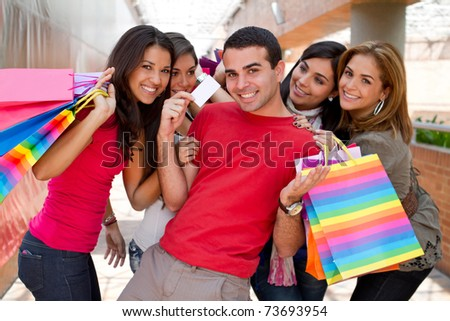 Group of happy shopping people and a man holding a credit card