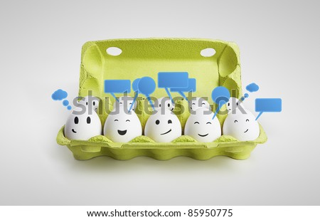 Group of happy smiling eggs with social chat sign and speech bubbles.  Ten white eggs in a carton box representing a social network. On a gray background - stock photo