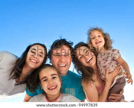Group of happy smiling friends: man, women and kids having fun outdoors against blue sky background. Summer vacations concept - stock photo