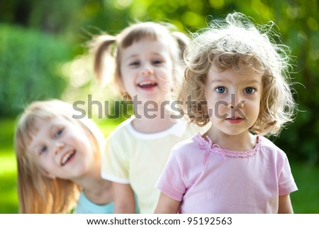 Group of happy smiling friends playing outdoors in spring park - stock photo