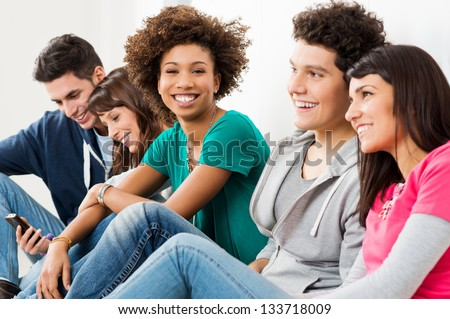 Group Of Happy Smiling Friends Sitting In A Row - stock photo