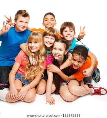 Group of happy smiling kids sitting together and playing - boys and girls black and Caucasian, hugging together - stock photo