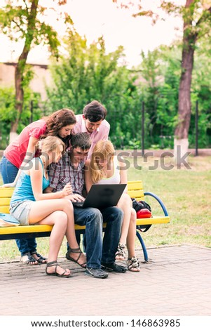 Group of happy smiling Teenage Students looking in laptop - stock photo