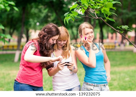Group Of happy smiling Teenage Students outdoor Using Mobile Phone - stock photo