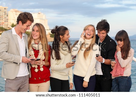 group of happy smiling teens, kids, texting and calling with mobile or cell phones. - stock photo