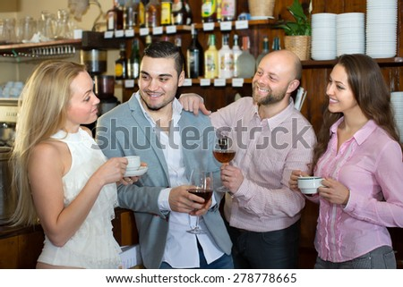 Group of happy smiling young adults chatting at bar. Focus on guy - stock photo