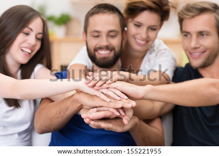 Group of happy smiling young friends stacking hands in a joint effort of cooperation and teamwork with focus to their hands - stock photo