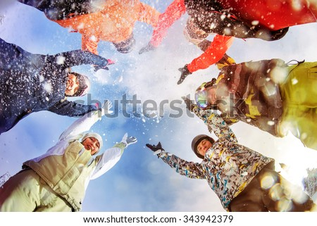 Group of happy snowboarders and skiers having fun and throwing up snow - stock photo
