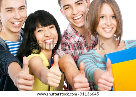 Group of happy students giving the thumbs-up sign - stock photo