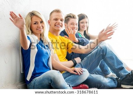 Group of happy students on a break waving. Focus on a boy and a girl. Background is blurry.