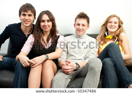 Group of happy students sitting on a sofa - stock photo