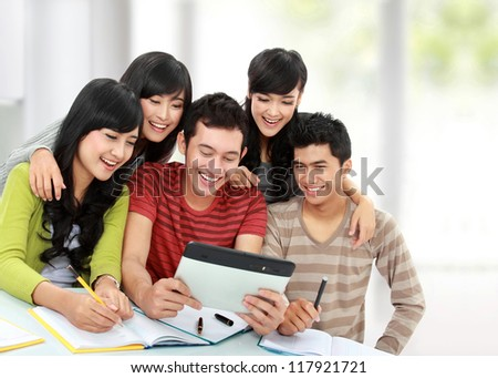 Group of happy students using tablet computer together