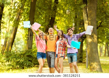 group of happy students with books in the Park on a Sunny day - stock photo