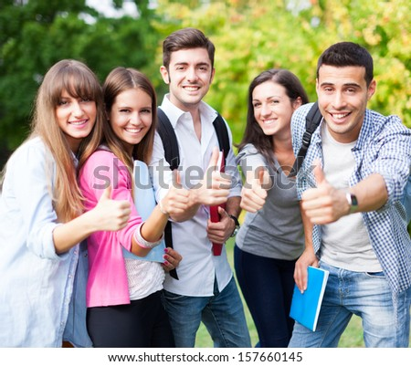 Group of happy students with thumbs up - stock photo