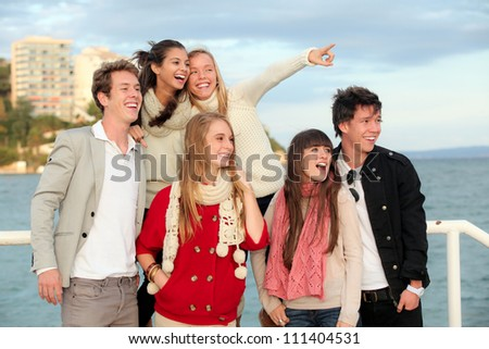 group of happy surprised teens or young people pointing and smiling - stock photo