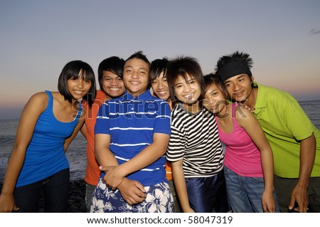 group of happy teen friends at the sunset beach