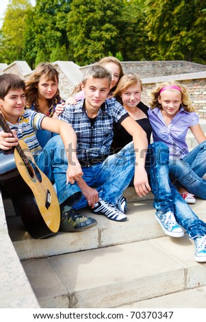 Group of happy teenage friends sitting on stairs with guitar - stock photo
