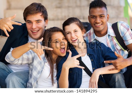 group of happy teenagers giving cool hand signs - stock photo