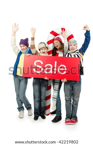 Group of happy teenagers holding christmas sale board.