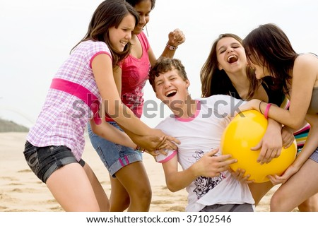 group of happy teens playing beach ball