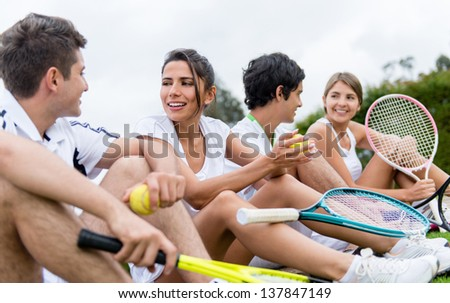 Group of happy tennis players resting outdoors